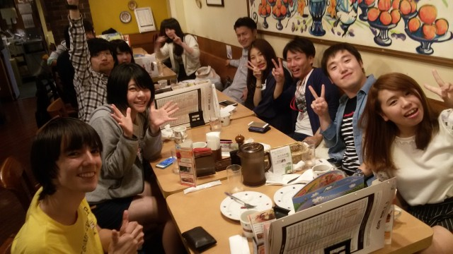International and Japanese students posting for a photo at a restaurant dinner table.