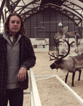 Sean visiting a reindeer at a farm.