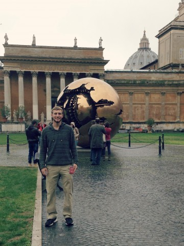 David standing in front of a spherical art sculpture.